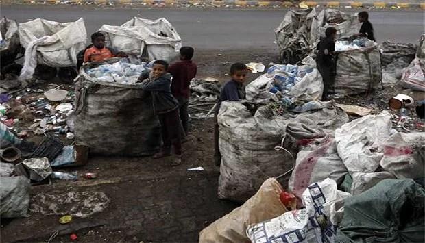 Crianças colectando bidons no lixo