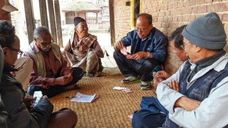 Groupe d'hommes âgés jouant aux cartes sous un balcon à l'abris des intempéries à Bhaktapur au Népal