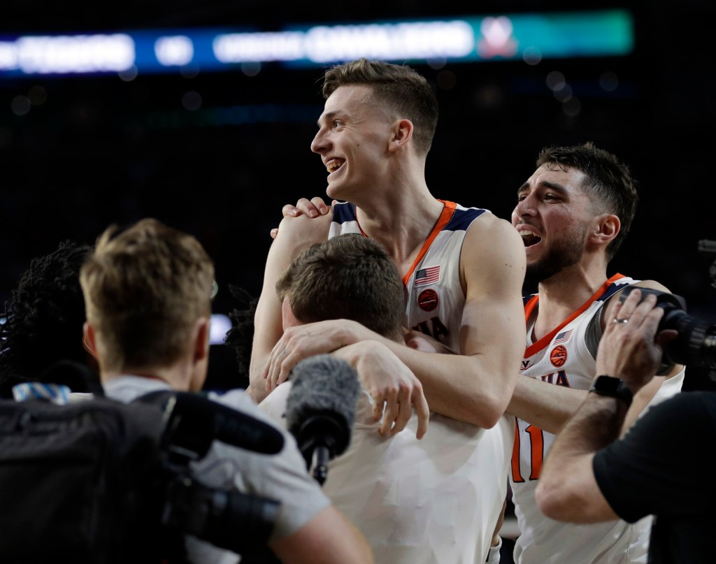 Virginia's Kyle Guy is mobbed by teammates after his three foul shots with 0.6 seconds left gave the Cavaliers a 63-62 win over Auburn in the Final Four on Saturday in Minneapolis.