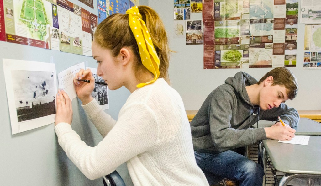 Students Laura Ireland, left, and Aric Belanger make notes on what they think is happening in World War II photos posted around Shane Gower's classroom on Wednesday at Maranacook Community High School in Readfield.