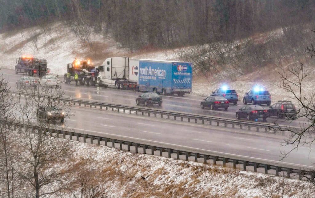 Workers connect a tow truck to a tractor-trailer that was in a crash involving multiple vehicles at mile marker 34 in the northbound lane of the Maine Turnpike in Saco on Monday morning.