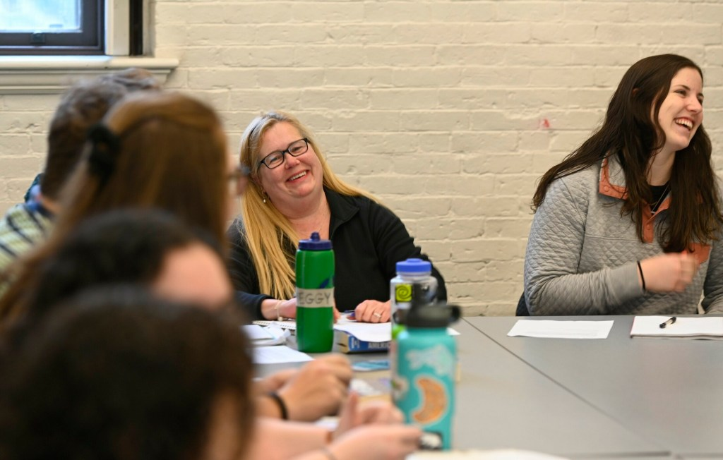 Lisa Bouffard shares a laugh with fellow students during a Christianity class at Bowdoin College in late April. After 18 years of taking one class per semester. Bouffard, who also works in the college's dining services  department, will graduate.