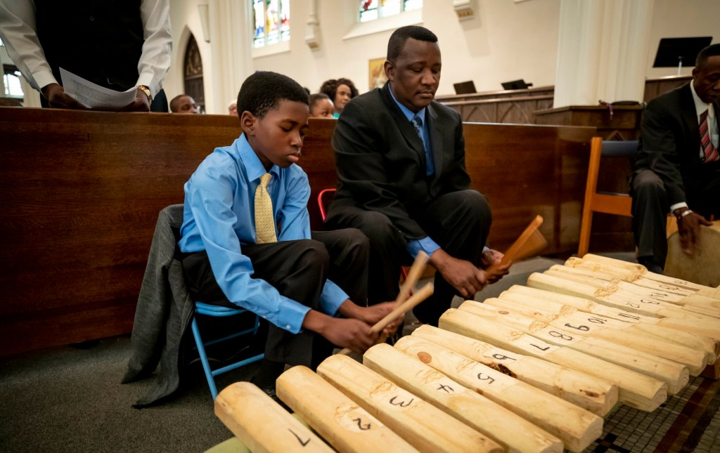 Victor Tartizio, 13, and his father, Dennis, play the ngbaningbo Sunday during an Azande Mass for members of Greater Portland's Sudanese community at the Cathedral of the Immaculate Conception in Portland.