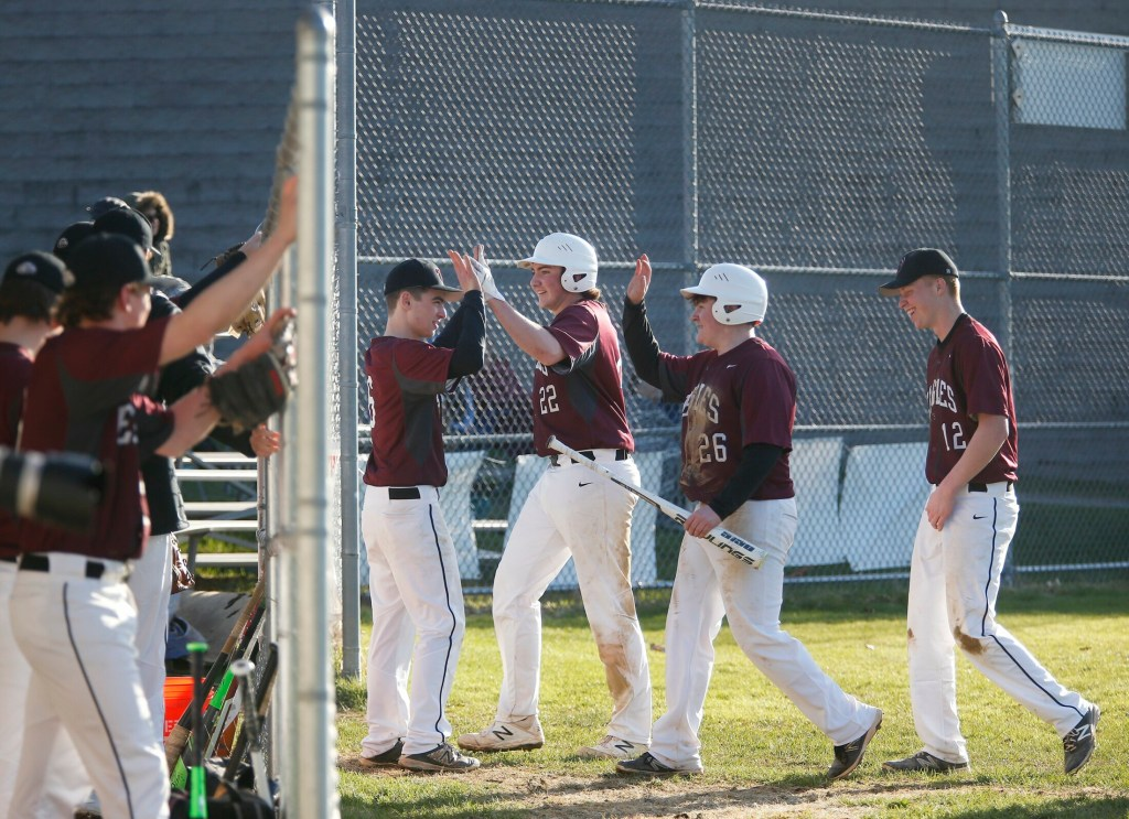 Nolan Kent celebrates with teammates Bryce Afthim  and Caleb McCartney  after they scored in the sixth inning of the Eagles' 9-4 win over Falmouth on Tuesday in Falmouth.