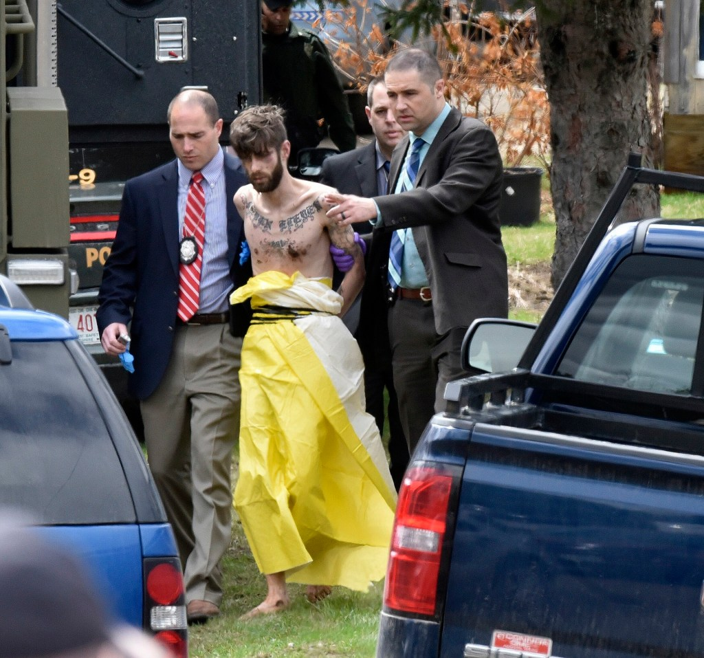 John D. Williams is led by Maine State Police detectives into a cruiser after he was apprehended April 28, 2018, in Fairfield.
