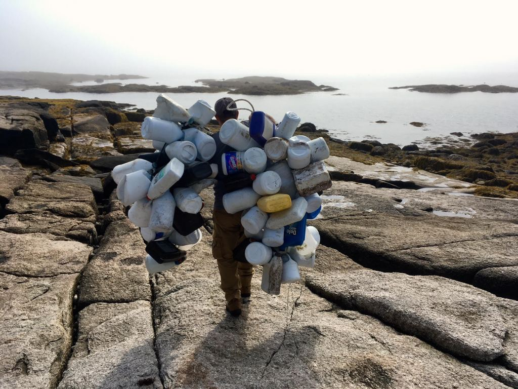 "Brian Marcaurelle cleans ocean-borne plastics debris from a Maine island. ""The fight to keep the Maine coast free of plastic trash has a hero in Brian Marcaurelle, a champion of sustainable recreation in Maine,"" his nomination for a 2019 Source Award said. In 2018, he oversaw efforts to remove more than 1,200 bags of garbage from Maine islands."