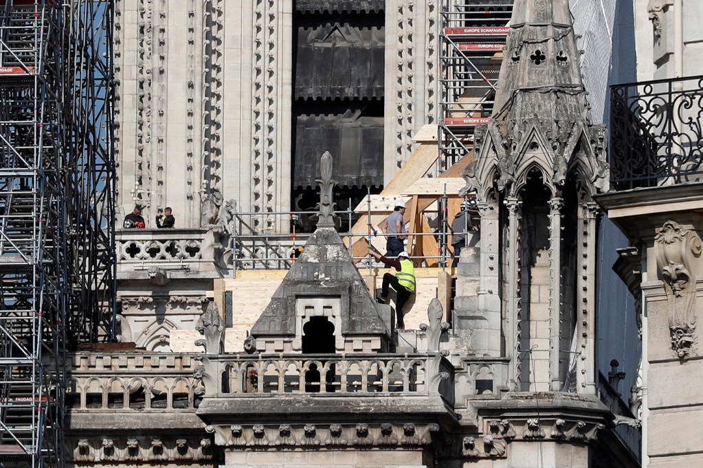 Workers stand by wooden planks supporting Notre Dame cathedral on Friday.