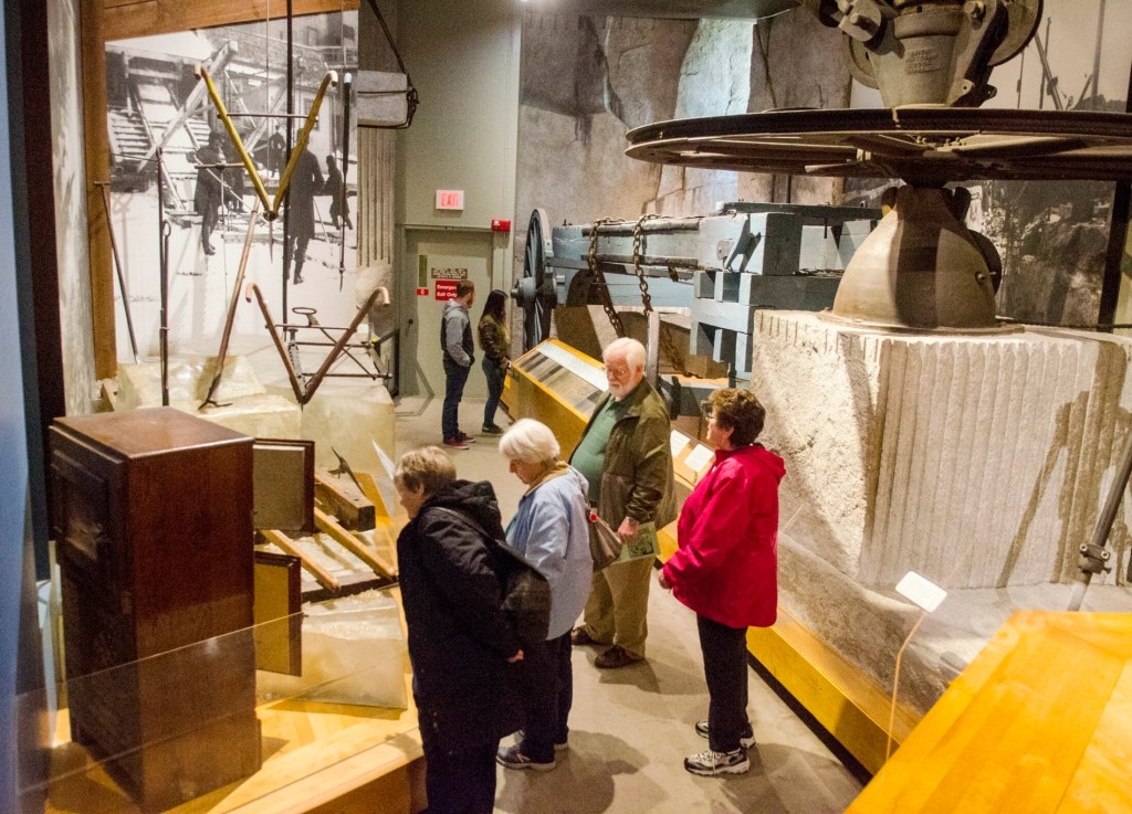 People look at display about ice harvesting and granite quarrying on May 1 at the Maine State Museum in Augusta.