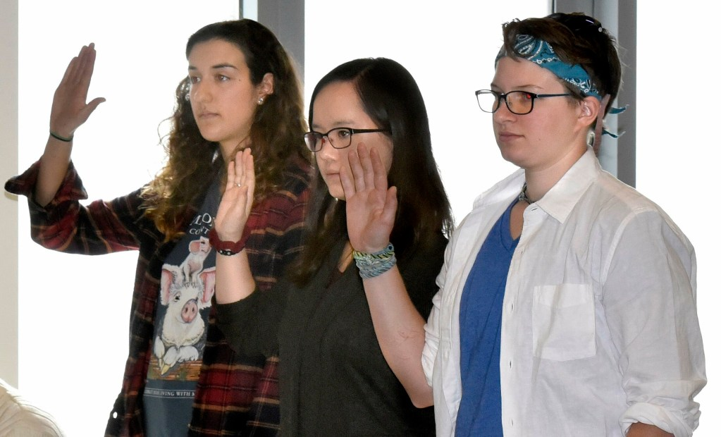 Colby College students, from left, Anna Braverman, Lutie Brown and Colleen George are sworn in to testify before the  Waterville Voter Registration Appeals board during a hearing in Waterville regarding voter eligibility on May 1.