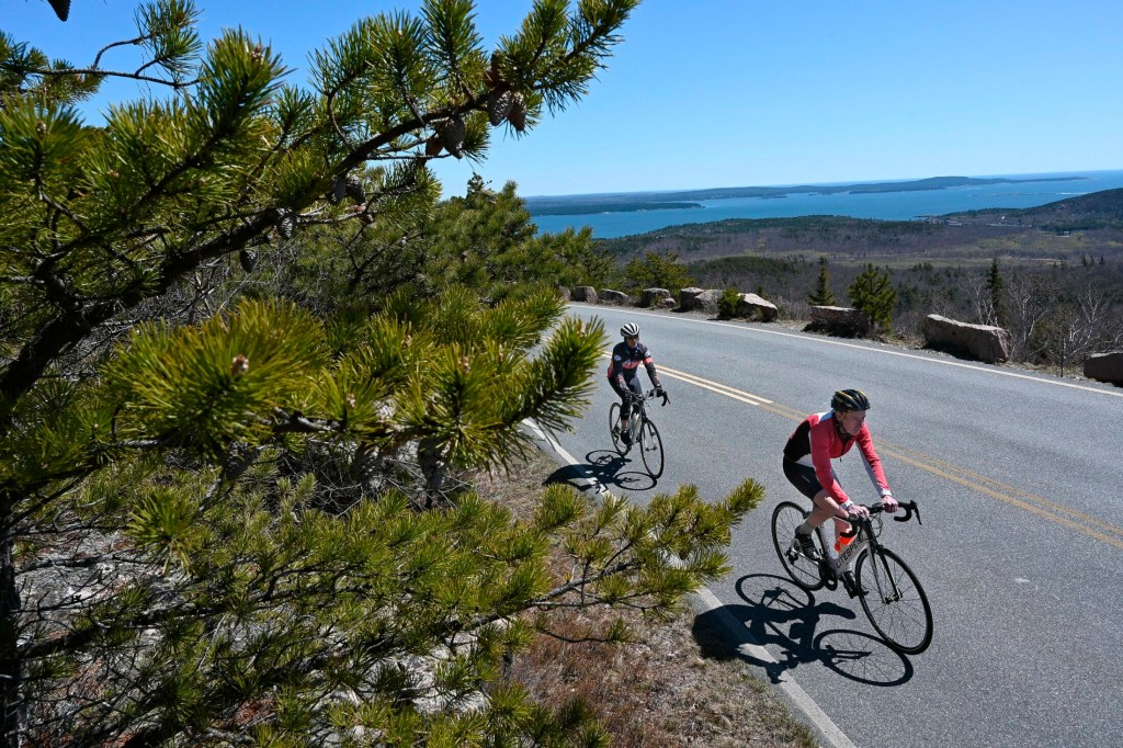 Biking enthusiasts Dean Read, left, and Bob Carroll bike up Cadillac Mountain in early May. It took them just 23 minutes to reach the summit.