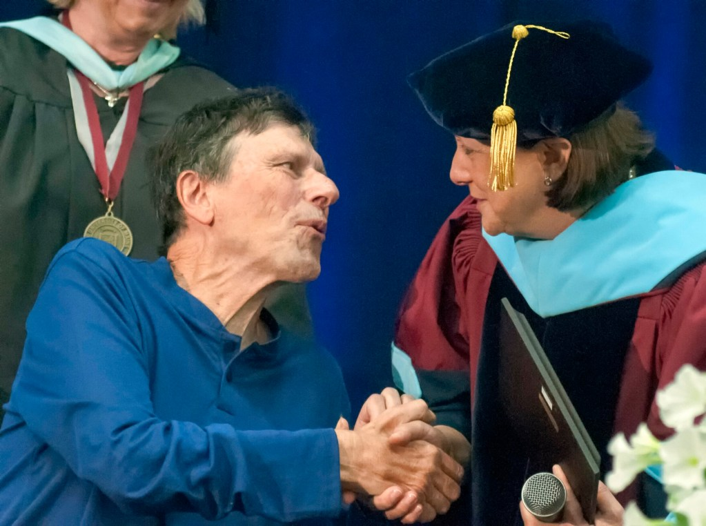 George Smith shakes hands with University of Maine at Augusta President Rebecca Wyke after receiving the Distinguished Achievement Award on Saturday during UMA's commencement ceremony at the Augusta Civic Center.