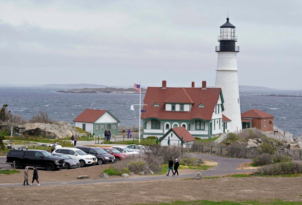 People visit Portland Head Light at Fort Williams Park in Cape Elizabeth on Monday. The Town Council decided Monday night to start charging people from out of town to park in the lots closest to the lighthouse and scenic paths, to fund the park's operations.