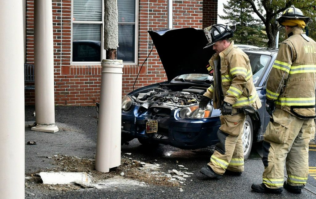 Waterville firefighters inspect damage to the entryway support columns Wednesday at Mount Saint Joseph Nursing Home in Waterville after the car in the background struck one of the columns.