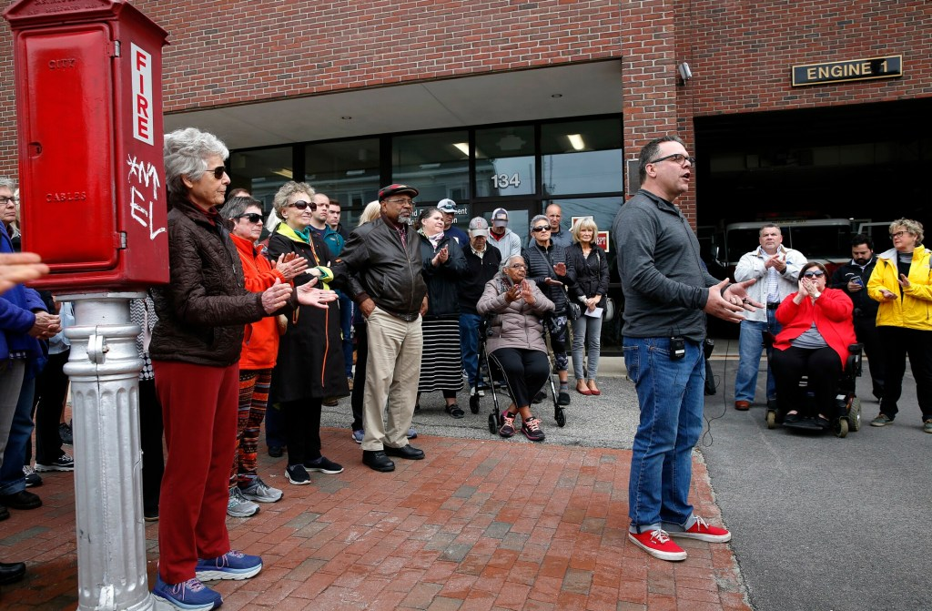 State Rep. Mike Sylvester, whose district includes Munjoy Hill, is flanked by about 30 people outside the neighborhood's fire station Friday to protest a city budget proposal that would decommission the station's Engine 1 and reassign its crew.