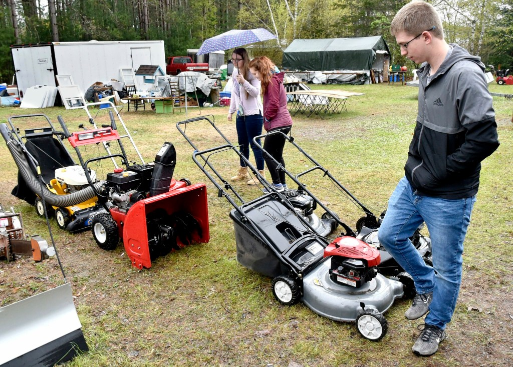 Brady Murray looks over lawn mowers for sale Sunday at a residence in Skowhegan during this year's 10-Mile Yard Sale. His friends Alyssa Watrous, left, and Cassidy Hamm also look around for deals.