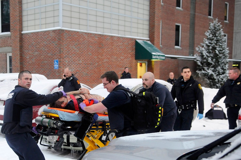 Firefighters and police escort Jason Begin after he was shot by Augusta police Officer Laura Drouin on Jan. 12, 2015, during a confrontation at an office at the Ballard Center — the former MaineGeneral Medical Center — in Augusta.