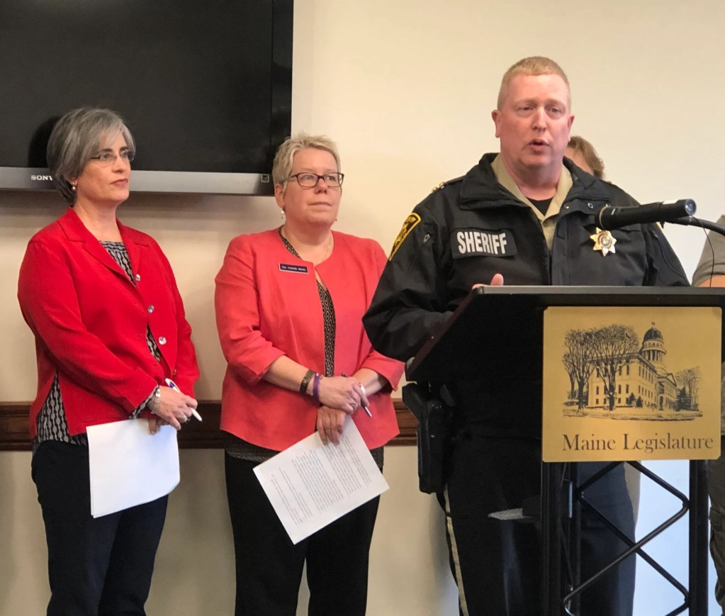 Penobscot County Sheriff Troy Morton speaks Wednesday in favor of a bill that would form a working group to review problems and recommend solutions for Maine's ailing mental health care system. Behind Morton are the bill's sponsors, Sen. Cathy Breen, D-Falmouth, left, and Rep. Charlotte Warren, D-Hallowell.