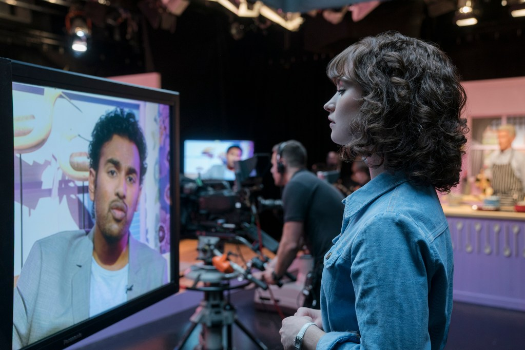 "Himesh Patel, left on TV screen, and Lily James star in ""Yesterday."" MUST CREDIT: Jonathan Prime, Universal Pictures"
