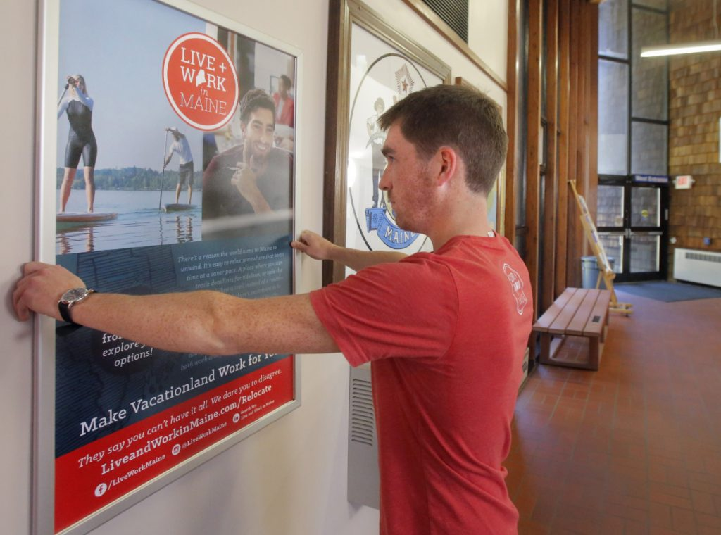 Nate Wildes of Live and Work in Maine sets up a poster at the Kittery information center in 2016.