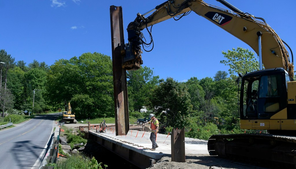 A Wyman and Simpson worker guides a pier into place to support the temporary bridge spanning the headwaters of Echo Lake in Mt. Vernon in June. The Richmond construction company is replacing the old bridge on Route 41 for the Maine Department of Transportation. The DOT is hoping $105 million in bonds will get legislative backing before the end of the month so they can go on November ballots. If passed, the bonds would provide money for next year's transportation projects.
