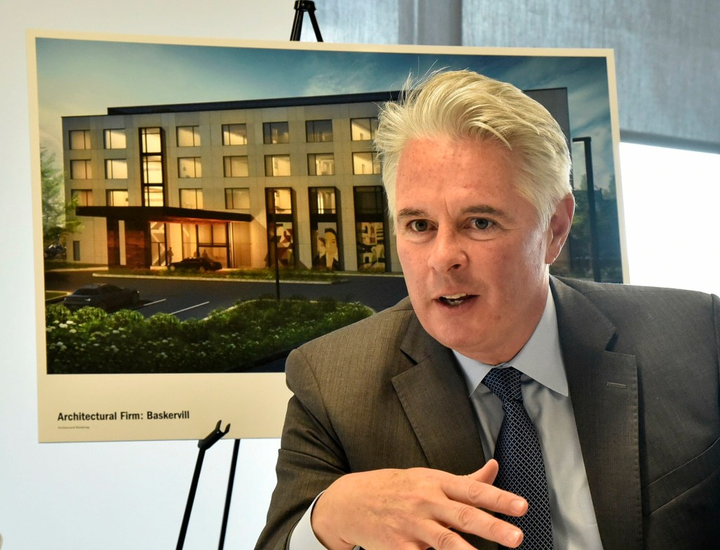 Speaking before an architect's rendering of The Lockwood Hotel, David Greene, president of Colby College, on June 3 outlines plans for the hotel that will be built in downtown Waterville.