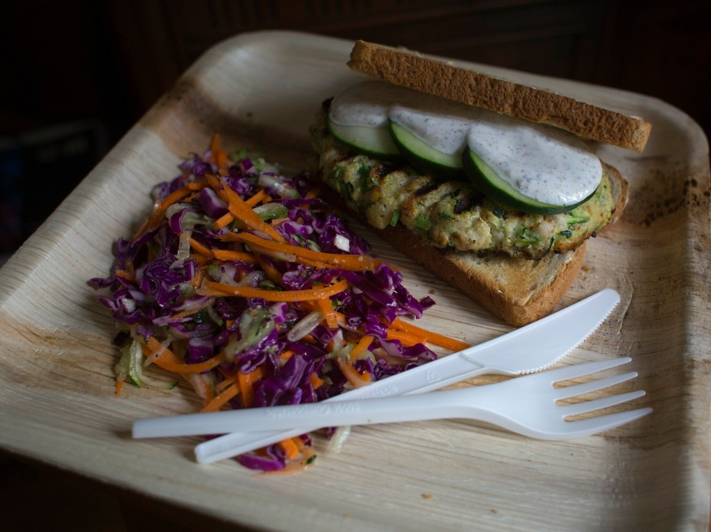 A chicken-zucchini burger on a bamboo plate. What are the greenest options for disposable dishware?