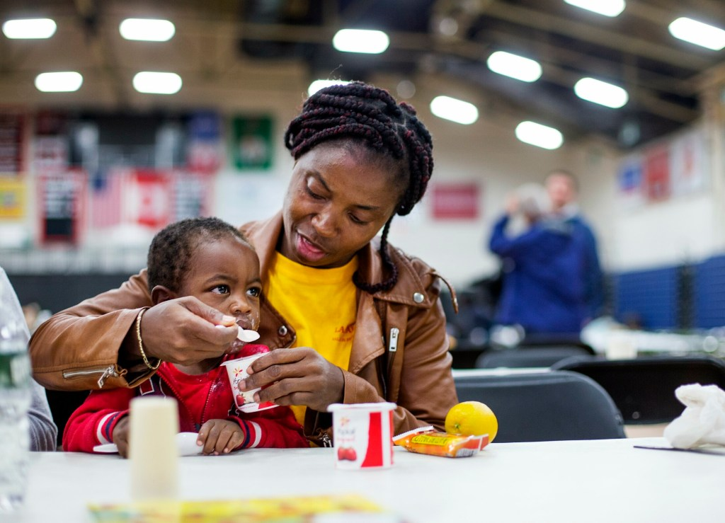 An asylum seeker from Cameroon, who did not want to give her name, feeds her son on June 13 at the emergency shelter the city has set up for asylum seekers at the Portland Expo.