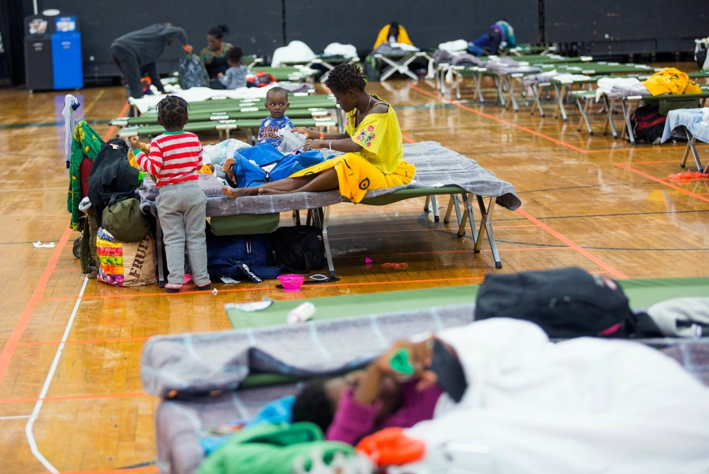 Families rest on cots last week at the emergency shelter for asylum seekers at the Portland Expo.
