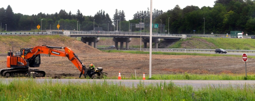Workers attend to a feller buncher Thursday on the southbound on-ramp to Interstate 95 off Western Avenue in Augusta. the Maine DOT recently cleared all the trees between the exit and on ramps at Exit 109.