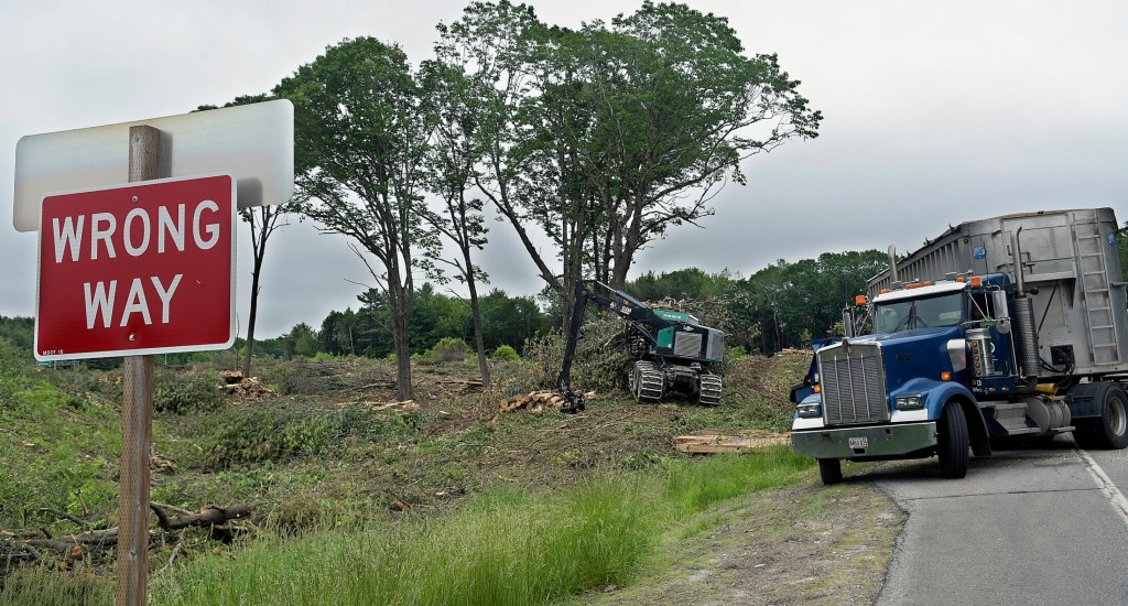 Loggers chip wood felled at Exit 112A Thursday in Augusta off Interstate 95. The Maine DOT recently clear cut and stumped all the trees between the exit and on ramps at 112B.
