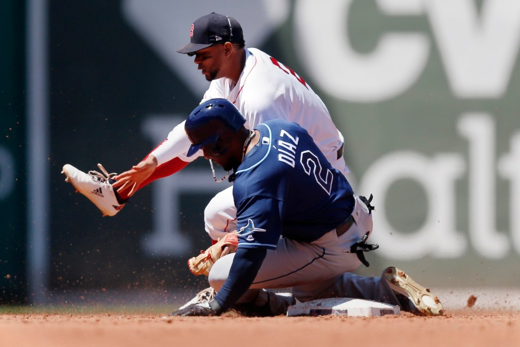Tampa Bay's Yandy Diaz slides into Red Sox's shortstop Xander Bogaerts but is called out on the play trying to stretch a single into a double during the Rays' 9-2 win in the first game of a doubleheader Saturday at Fenway Park in Boston.