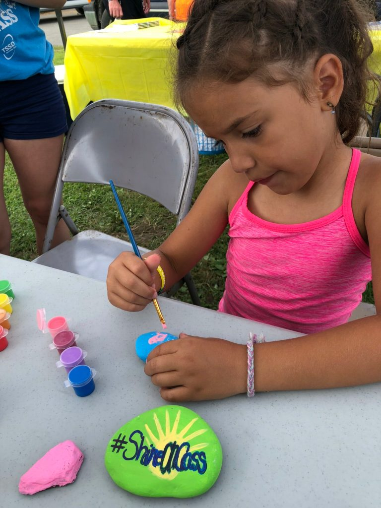 Avery Charland paints kindness messages on rocks to share in her community at last year's ShineOn Oakland Day. Kindness projects will be part of a full field of free children's activities planned for Oakfest 2019, including carnival games, bounce houses, slides and more, July 27, on the grounds of Williams Elementary School in Oakland.