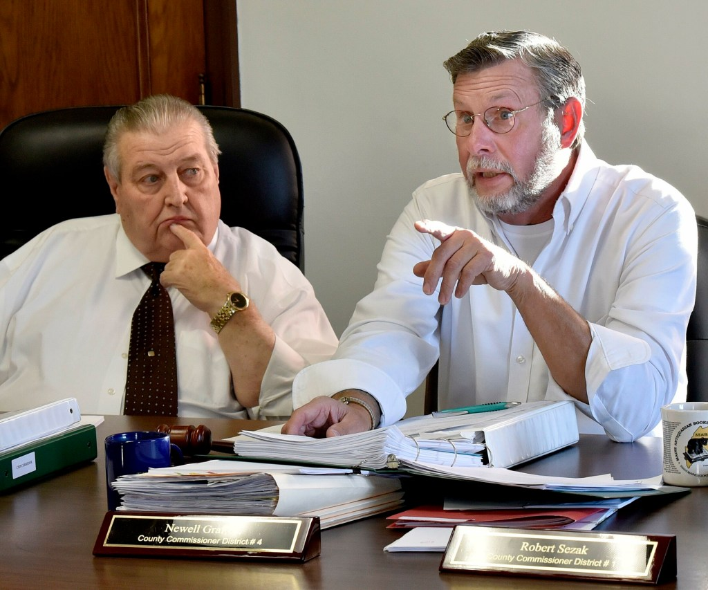 Somerset County Commissioner Newell Graf Jr., right,  speaks to an opponent of the CMP corridor project Nov. 7, 2018, during a sometimes heated meeting in Skowhegan. At left is Commissioner Lloyd Trafton, who tendered his resignation from the board of Western Mountains & Rivers Corp. on Friday after he was accused of having conflict of interest. Western Mountains received $22 million from CMP to support its NECEC transmission line proposal through Somerset County.