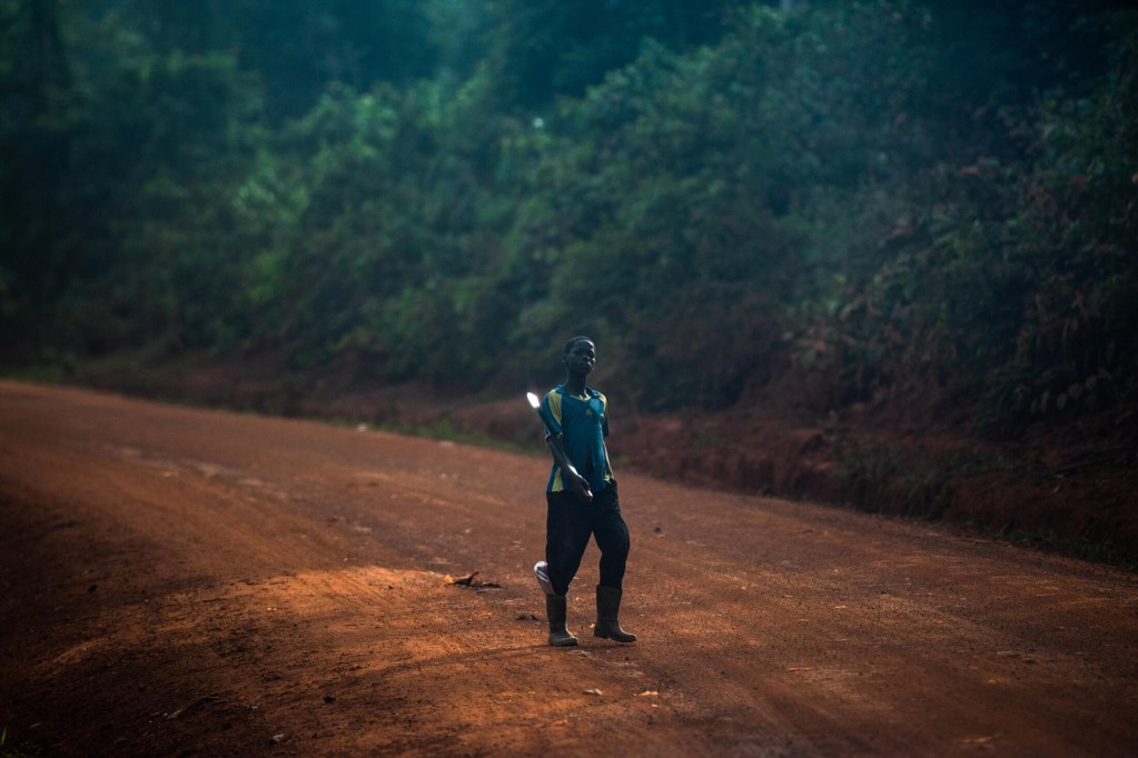 A boy holds his machete as he heads along a road to a cocoa farm.