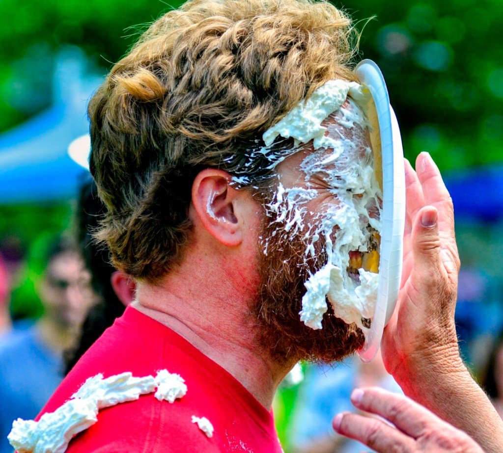 """Chase Morrill, of the """"Maine Cabin Masters"""" television show, gets hit in the face with a plate of whipped cream Saturday during the Strawberry Festival in Wayne. There was a raffle for a chance to hit a cast member with a pie."""