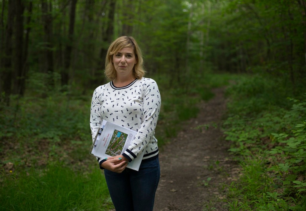 Elizabeth Rose is organizing opposition to a developer's proposal to rezone forestland near Morrill's Corner to allow construction of 20 duplexes. She is pictured Wednesday on Harvard Path, which would become a paved street behind her house.