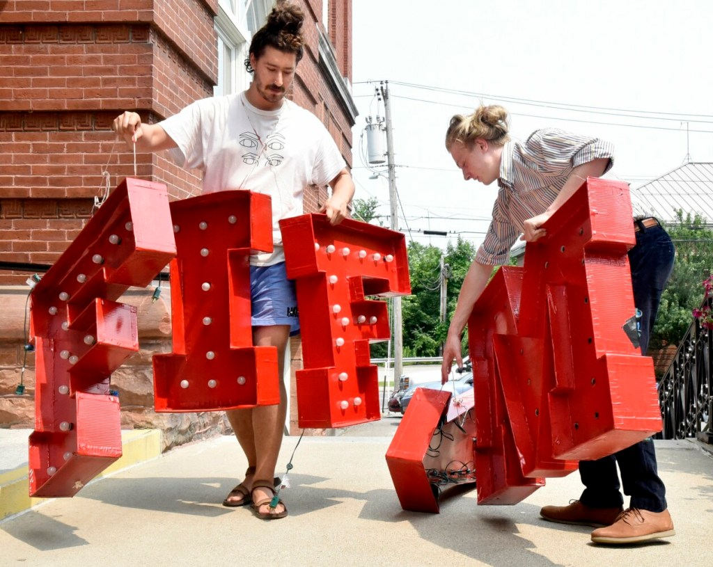 """Aaron Canter, left, and Tom Crisp arrange large red letters that spell """"MIFF,"""" the acronym of the Maine International Film Festival. The letters will be erected at the Waterville Opera House. That is one of the venues where films will be shown during the 22nd annual festival."""