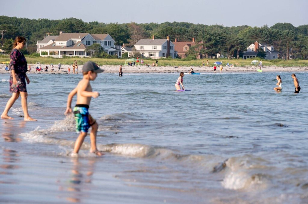 Swimmers enjoy the waves at Goose Rocks Beach in Kennebunkport this summer. The Maine Supreme Judicial Court upheld a lower court ruling that held there was no evidence the strip of sand was conveyed into private ownership in the deeds of the oceanfront property owners.