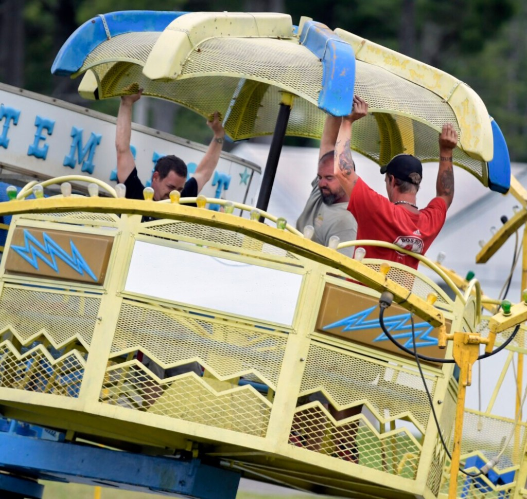 Workers with Kavanaugh Amusements assemble a ride Tuesday on the midway in preparation for the Pittston Fair.