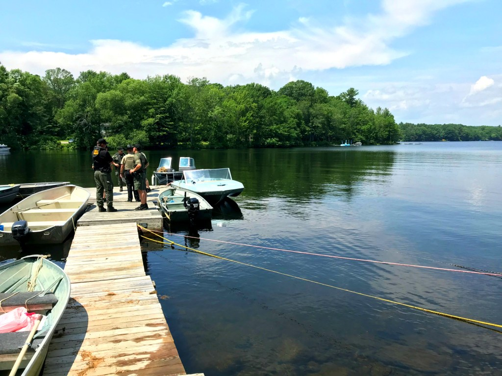 Wardens from the Maine Warden Service and Kennebec County sheriff's deputies stand on a dock Saturday morning near the location where Christopher Brown's body and boat were discovered.