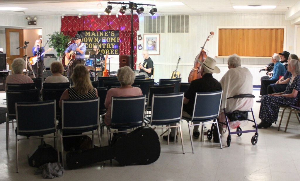 """Waterville-area residents listen to host Bob Heller perform traditional country music during a live taping of """"Maine's Down Home Country Jamboree"""" at the old Legion building on College Avenue Sunday night."""