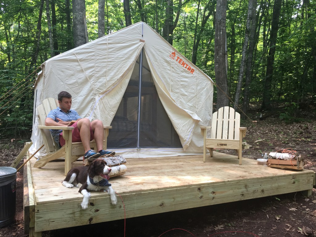 Nick DeBlois and his dog, Brooks, relax at a Tentrr campsite at Camden Hills State Park earlier in July. DeBlois and his wife, Katy, are longtime campers from Brunswick who had never been glamping before.