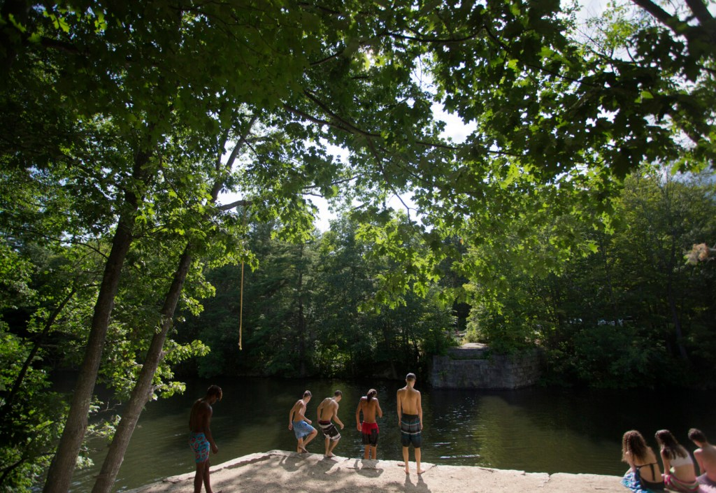 Teenagers gather Saturday at a popular swimming spot at Pleasant Point Park in Buxton, where many of the rope swings appeared to have been cut so they couldn't be used. Buxton's police chief said he would like to remove rope swings from the Saco River in town, though he would expect kids to put them up again.