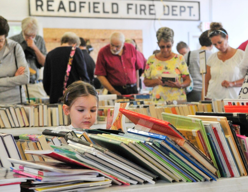 While adults browse in the background, Julia Henderson reads her book during the Readfield Community Library book sale on Aug. 8, 2015, during Readfield Heritage Days in Readfield.