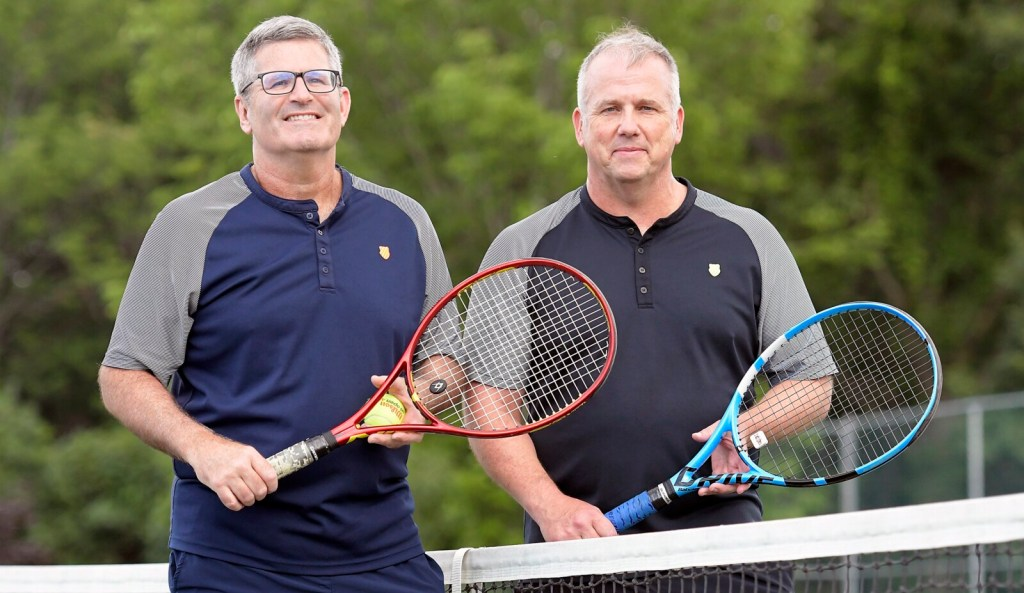 Mark Gelsinger, left, and Ken Wells stand at a tennis net near their home in Gardiner on Tuesday. The pair was recognized last month by the United States Tennis Association as the top-ranked doubles team in New England last year in the 45-and-over category.