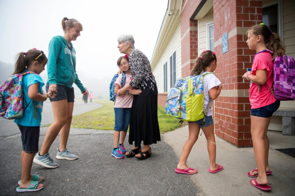 Helen Peavey gives a hug to Kylie Savage on Wednesday, the first day of school at Madison Elementary School. Peavey, a special ed paraprofessional, greets students arriving to school every day.