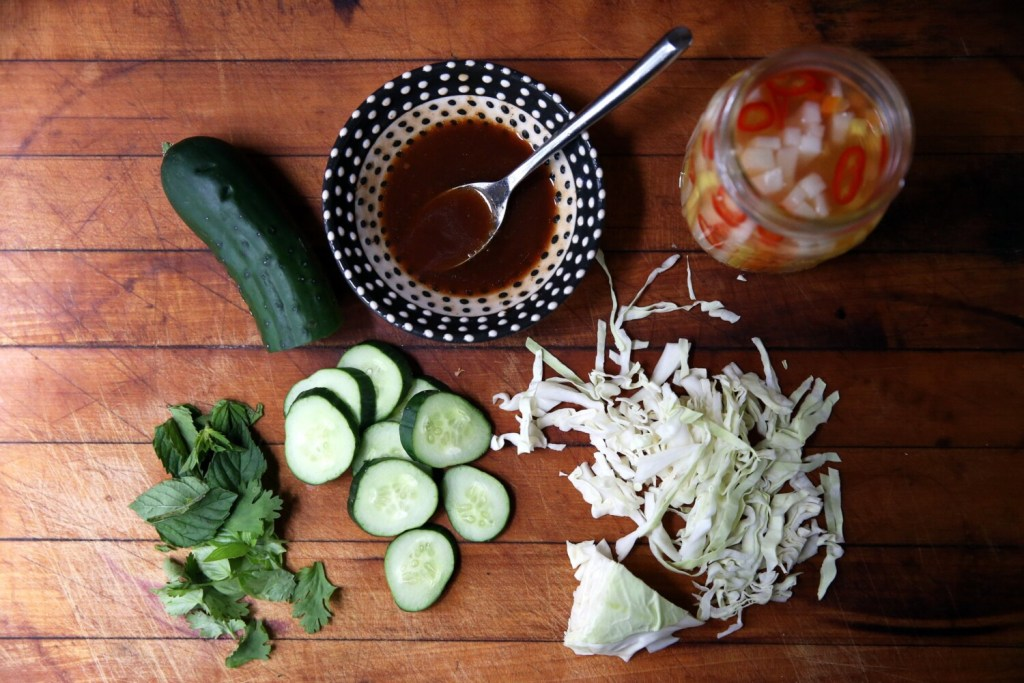 Mise en place for Owen's Vietnamese Chicken and Rice Bowl: cucumber slices; marinade; pickled kohlrabi, daikon radish, carrot and red chili pepper; sliced cabbage; and mixed fresh basil, mint and cilantro.