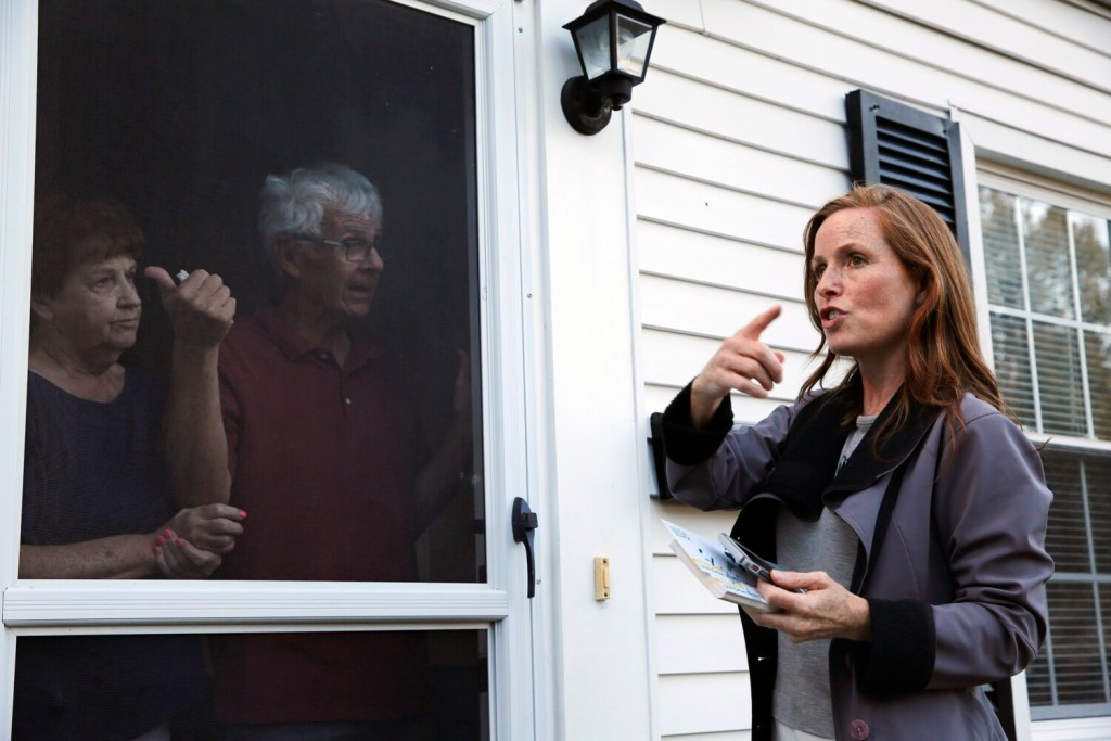 Portland mayoral candidate Kate Snyder talks about tight on-street parking with Libbytown residents Beverly and Dennis Moran while campaigning door-to-door last month.