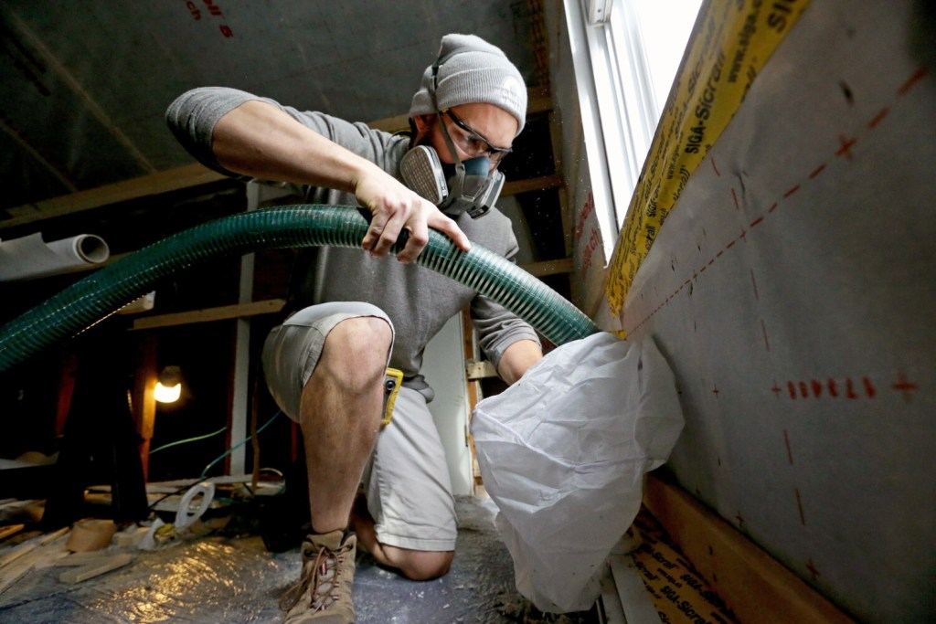 Cody Moreau, a worker from Horizon Homes, uses a hose to blow fill bays encased in a membrane with insulation in an attic in South Portland. Weatherizing homes will be necessary to reach Gov. Janet Mills ambitious climate change goals, but the industry is dealing with a tight labor market and the expense of some home projects.