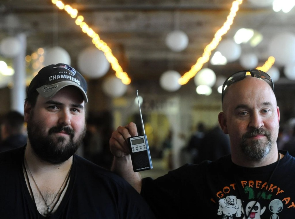Dustin Marcia, left, of the Central Maine Ghost Hunters, and Travis Hartford of Ghost Research and Investigations of Maine, are shown with a SB7 Spirit Box during Saturday's third annual Paranormal Festival at Olde Mill Place in Vassalboro. Marcia said the device is used in ghost hunts to gather voice information in real time.
